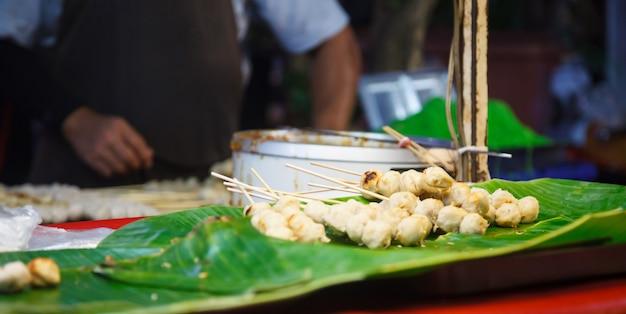 Gegrillte schweinefleisch-und rindfleisch-fleisch-ball-stöcke gesetzt auf grünes bananenblattregal in straßenlebensmittelmarktstall
