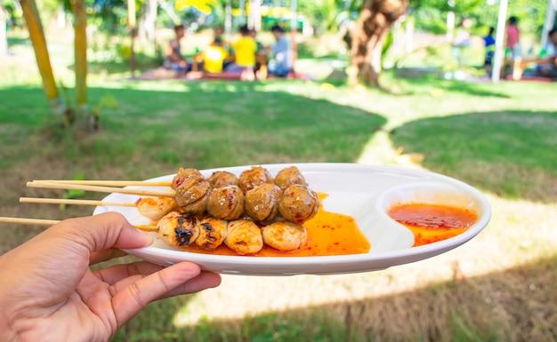 Gegrillte schweinefleisch- und rindfleischfleischklöschen mit meeresfrüchtesoße auf weißer plastikplatte in der hand hintergrund undeutliche touristen auf dem rasen.