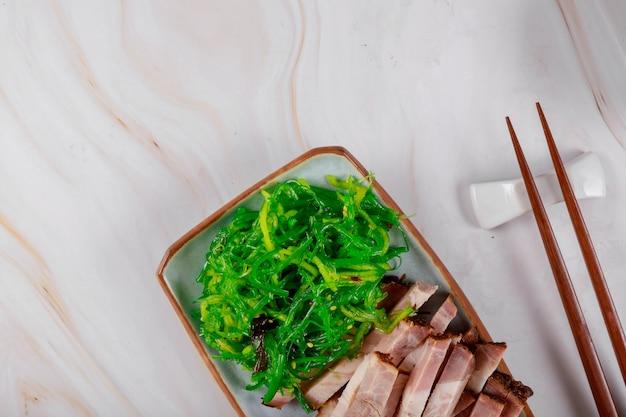 Gegrillte schweinefleischscheiben mit seetang und holzstäbchen