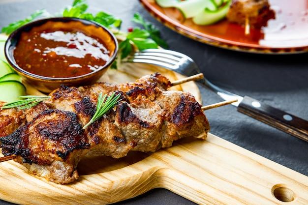 Gegrillte schweinefleischspieße mit gurkensalat und barbecue-sauce auf dem schneidebrett hautnah