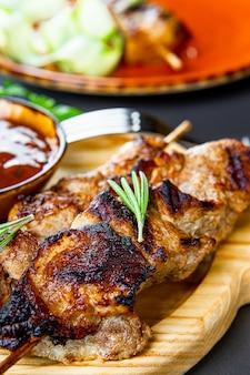 Gegrillte schweinefleischspieße mit gurkensalat und barbecue-sauce auf dem schneidebrett schließen vertikal