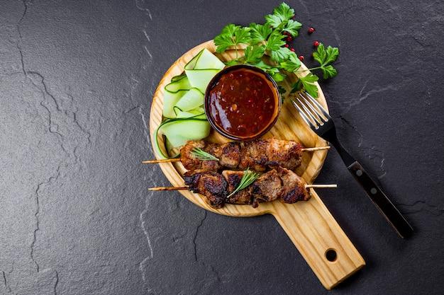 Gegrillte schweinefleischspieße mit gurkensalat und barbecue-sauce auf der draufsicht des schneidebretts, frei