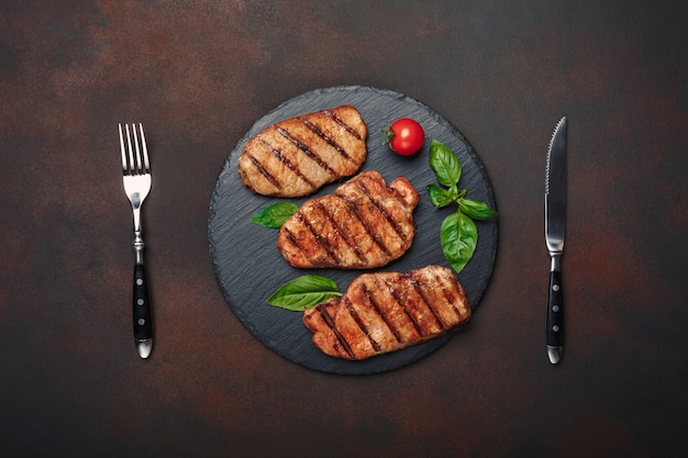 Gegrillte schweinefleischsteaks mit basilikum, tomaten, messer und gabel auf schwarzem steinigem und braunem rostigem hintergrund