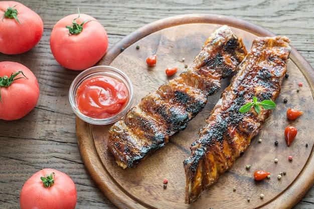 Gegrillte schweinerippchen mit tomaten auf dem holzbrett