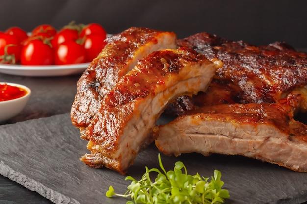 Gegrillte schweinerippchen, serviert auf einem graphitbrett mit tomaten