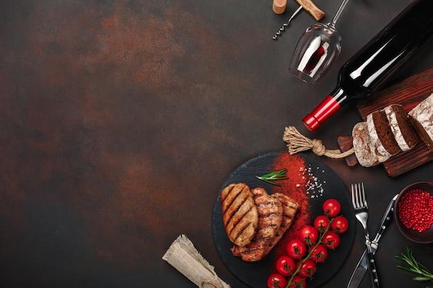 Gegrillte schweinesteaks mit flasche wein, weinglas, messer, gabel, schwarzbrot, kirschtomaten und rosmarin