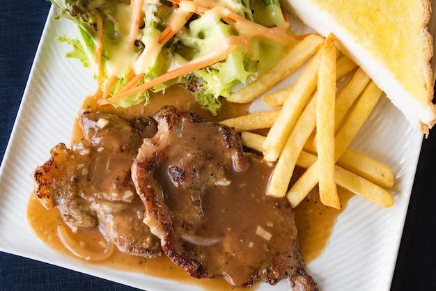 Gegrillte steaks, gekochte pommes frites und gemüsesalat