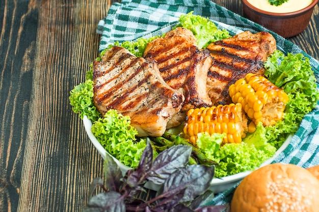 Gegrillte steaks mit kräutern und gemüse auf dunklem holzhintergrund. platz kopieren.