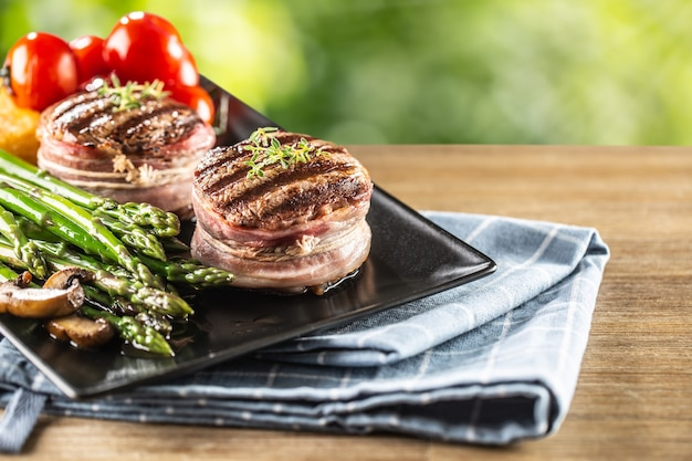 Gegrillte steaks serviert auf einem teller mit spargel und frischen tomaten.