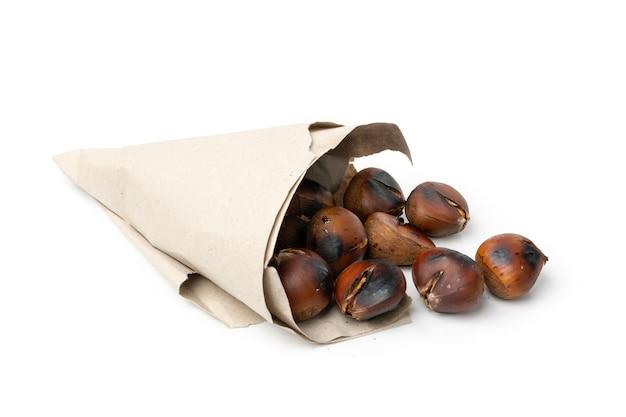 Gegrillte süße ganze kastanien in einer papiertüte isoliert