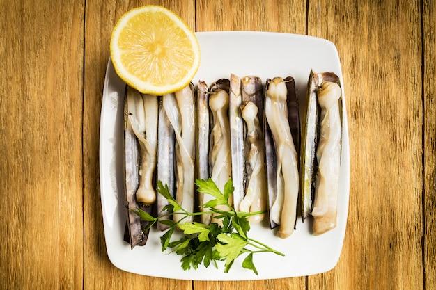Gegrillte taschenmesser mit petersilie und halber zitrone auf einer weißen platte