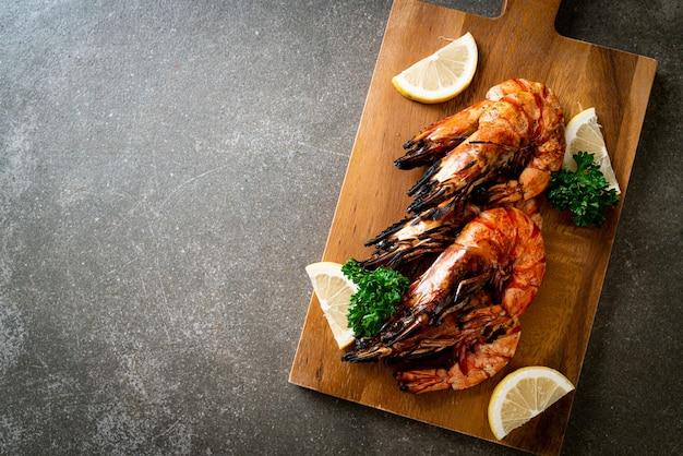 Gegrillte tigergarnelen oder shrimps mit zitrone auf holzbrett