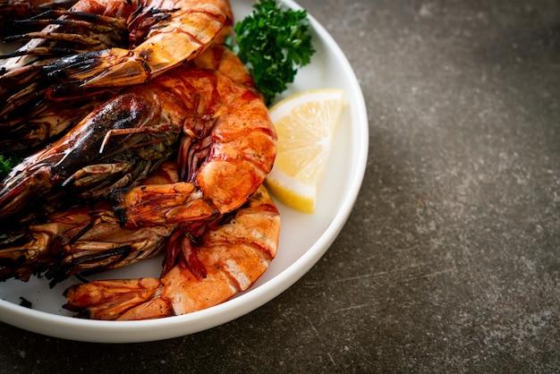Gegrillte tigergarnelen oder shrimps mit zitrone auf teller