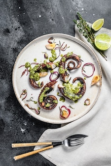 Gegrillte tintenfischtentakeln mit pesto, thymian und zwiebeln