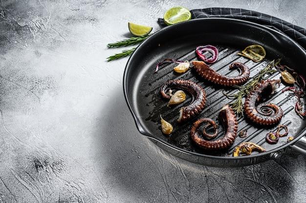 Gegrillte tintenfischtentakeln mit rosmarin, knoblauch und butter in einer pfanne