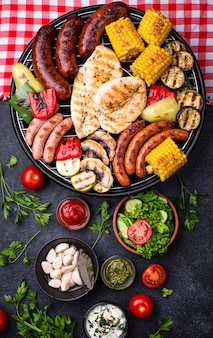 Gegrillte würstchen, fleisch und gemüse.