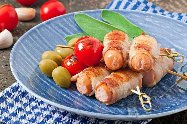 Gegrillte würstchen in speckstreifen mit tomaten und salbeiblättern gewickelt