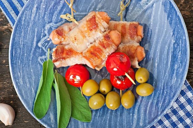 Gegrillte würstchen in speckstreifen mit tomaten und salbeiblättern