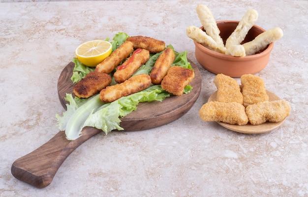 Gegrillte würstchen, käsesticks und chicken nugges auf einem salatblatt.