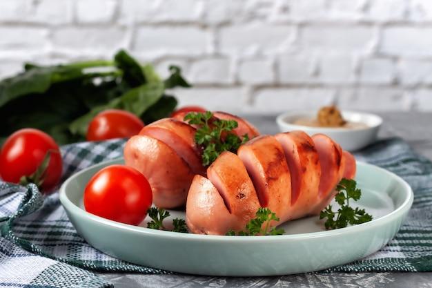 Gegrillte würstchen mit frischem gemüse liegen auf der platte