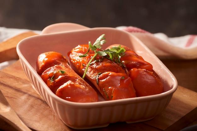 Gegrillte würstchen mit sauce ketchup auf einem holztisch