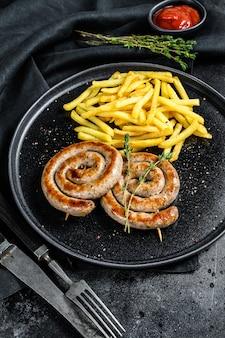Gegrillte würstchen mit schweinefleischspirale und einer beilage aus pommes frites