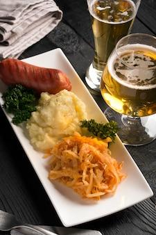 Gegrillte würstchen und kartoffeln mit einem glas bier