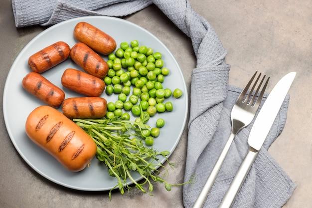 Gegrillte würste grüne erbsenerbsensprossen auf grauem teller