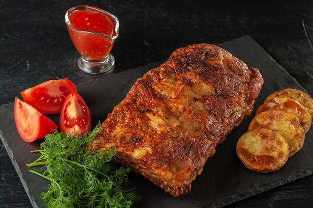 Gegrillte würzige rippchen, serviert mit scharfer chilisauce und frischen tomaten