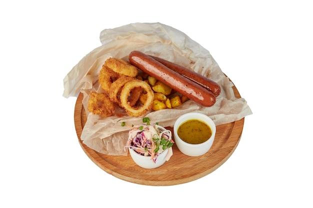 Gegrillte wurst mit kartoffelpommes und paprika, ketchup, auf weißem teller, isoliert auf weiß