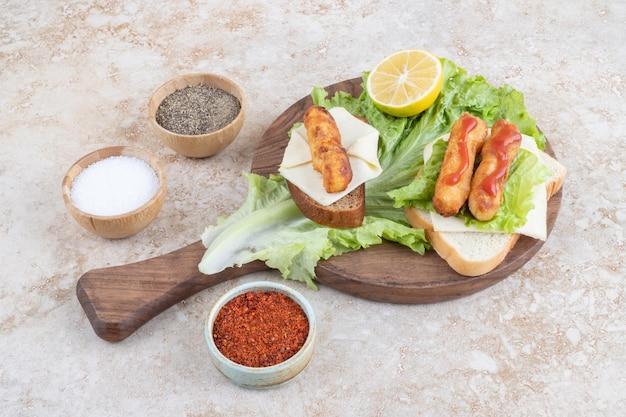 Gegrillte wurststicksandwiches mit kräutern, käse und soßen.