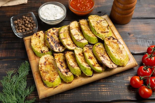 Gegrillte zucchini auf schneidebrett mit soße auf dunklem holztisch