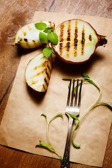 Gegrillte zwiebel serviert mit frischem basilikum