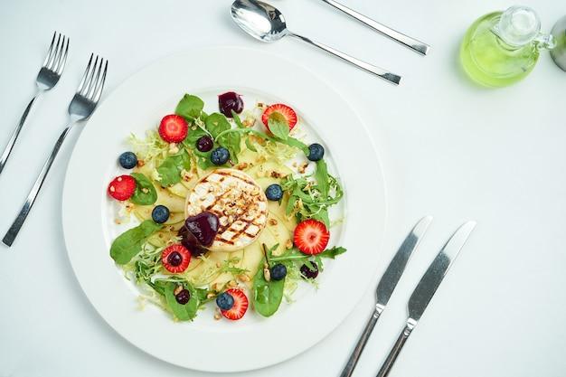 Gegrillter camembertkäse mit äpfeln, erdbeeren und blaubeeren in einem weißen teller auf weißem teller