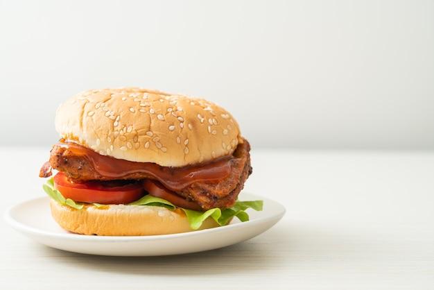 Gegrillter chicken burger mit sauce auf weißem teller