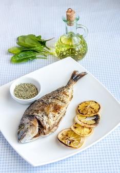 Gegrillter dorada-fisch mit zitrone und spinat