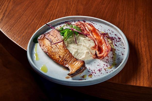 Gegrillter eryngii-pilz mit kimchi-kohl und selleriepüree, serviert in einem weißen teller auf einem holztisch. restaurant essen. nahaufnahme ansicht gegrillte scheiben von könig-austernpilzen