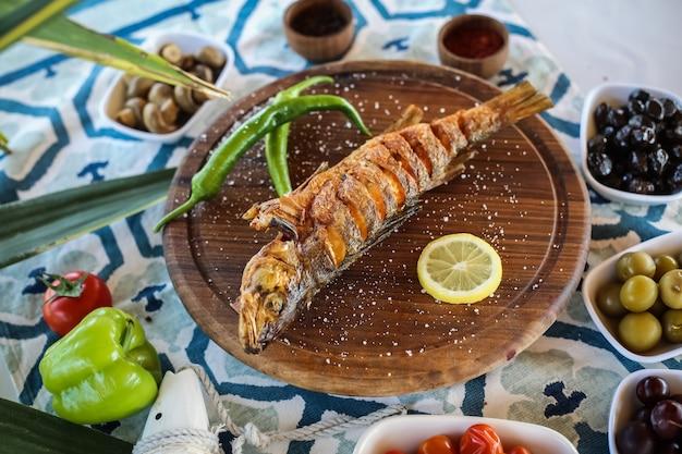 Gegrillter fisch auf dem holzbrett gesalzene zitronengurken