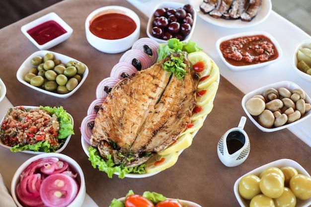 Gegrillter fisch auf dem holzbrett gesalzener zitronengurken-zwiebelsalat