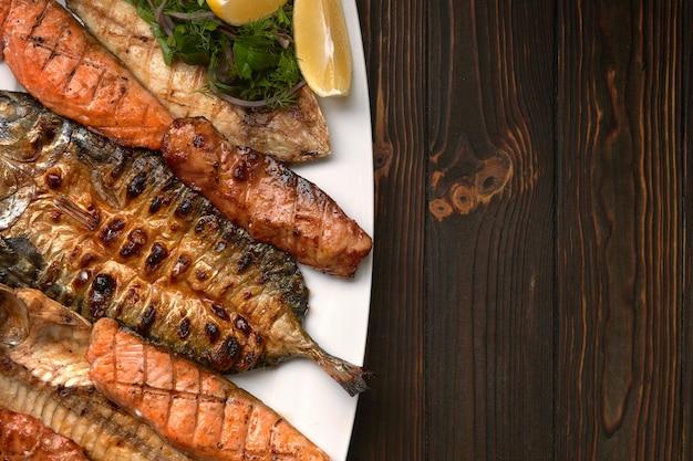 Gegrillter fisch auf einem weißen teller mit kräutern und zitrone