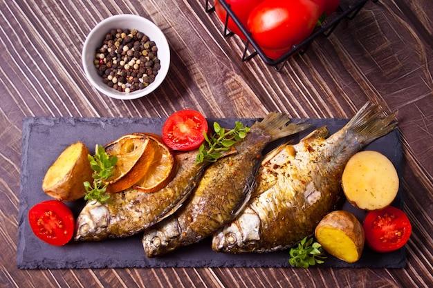 Gegrillter fisch auf teller mit zitrone und gemüse