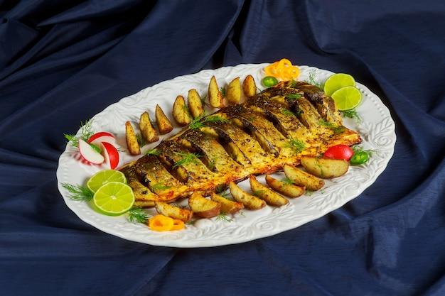 Gegrillter fisch mit bratkartoffeln und gemüse auf dem teller