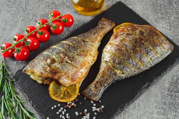 Gegrillter fisch mit gebraten mit zitrone, rosmarin, tomaten, olivenöl und gewürzen auf schwarzem schiefer, auf grauem hintergrund.
