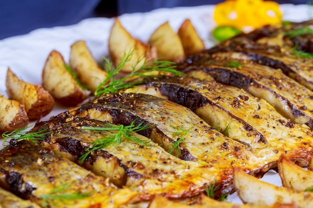 Gegrillter fisch mit gebratenen kartoffeln und gemüse auf der platte