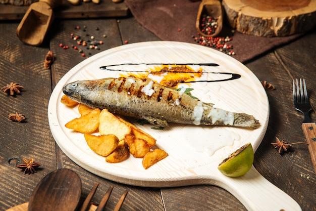 Gegrillter fisch mit kartoffeln auf dem holzbrett