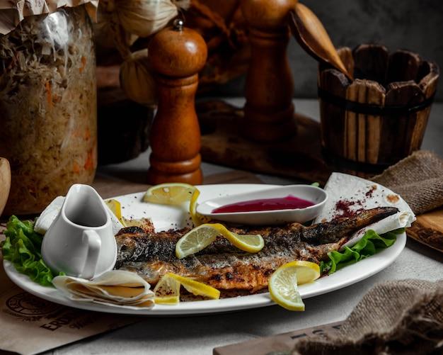 Gegrillter fisch mit zitrone und tomatensauce.