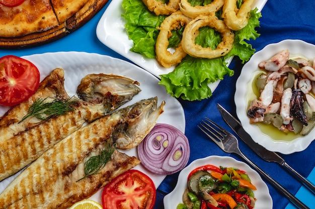 Gegrillter fisch-tomaten-zwiebel-kalamary-grüner salat von oben