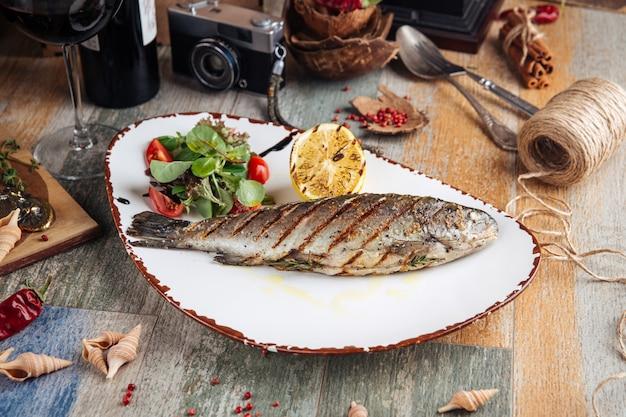 Gegrillter forellenfisch mit salat und zitrone