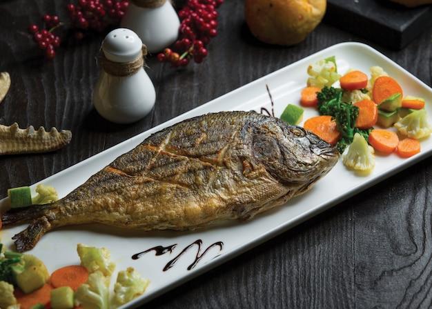 Gegrillter ganzer fisch mit blumenkohlkarottensalat