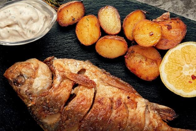 Gegrillter ganzer fisch serviert mit ofenkartoffeln, zitrone und sauce draufsicht.